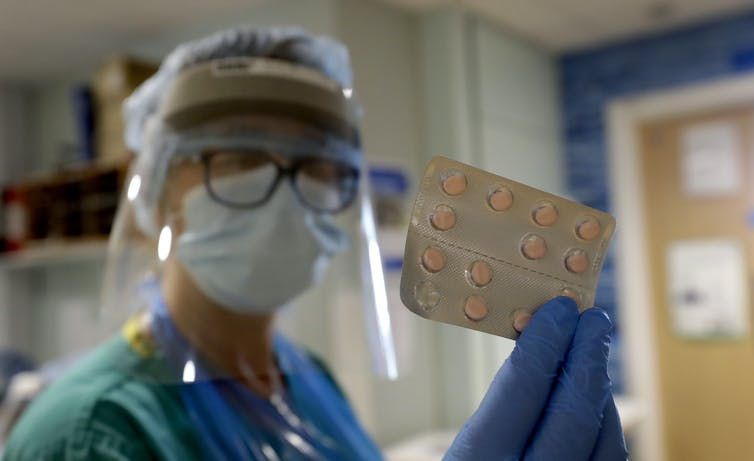A health worker in full PPE holds up a packet of pills.