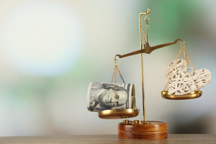 Two weighing scales, with a wad of money on one side, and a heart on the other side.