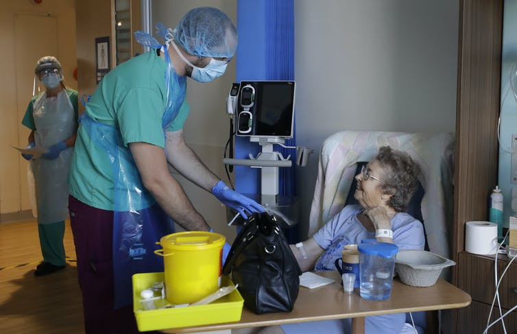A health worker in PPE tends to an elderly COVID patient in hospital.