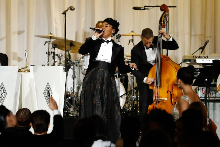 A woman on stage sings in a microphone with a viola player in front of a crowd.