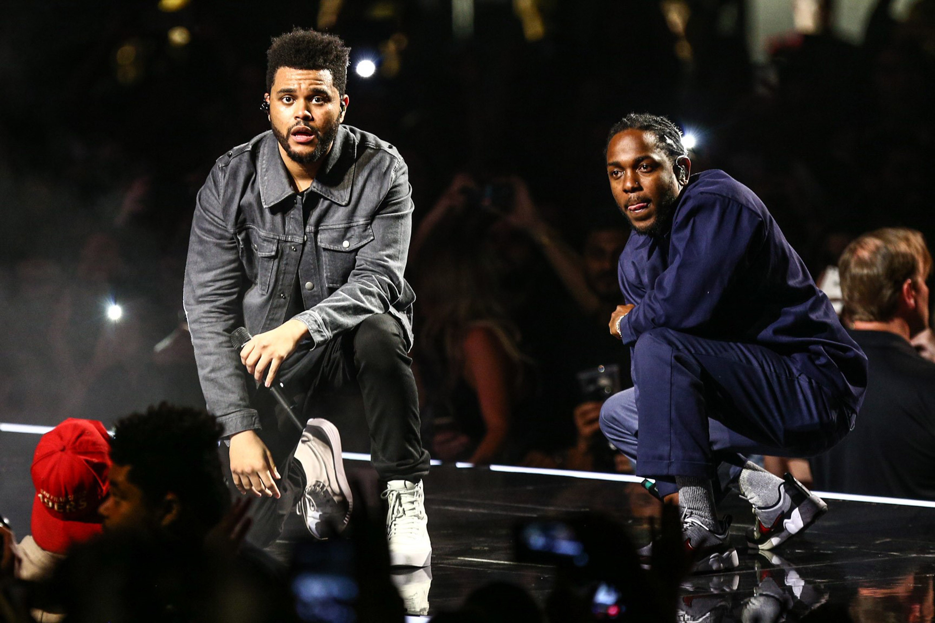Two rappers kneel on stage.