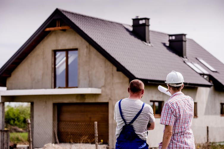 Two men stand in front of a residential construction site.