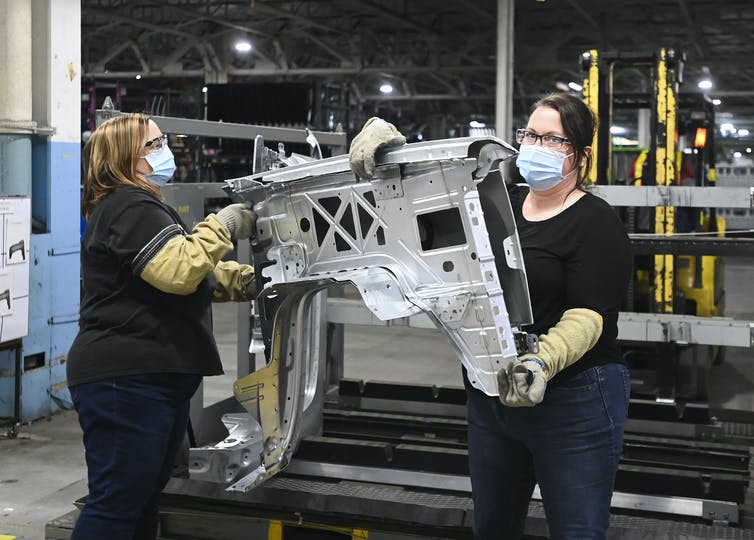 Two women GM workers carry truck fenders.