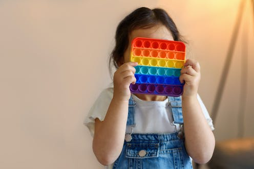Little girl in white shirt and blue overalls holding a multicolored square popping toy in front of her face