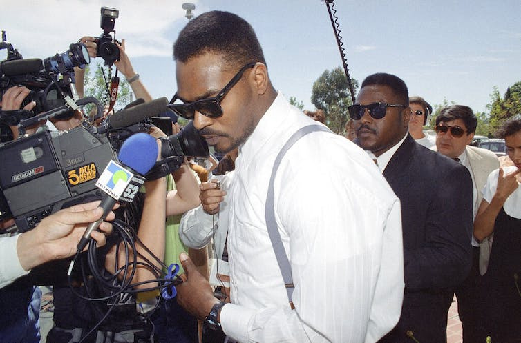 Rodney King squeezes past a crush of reporters and photographers
