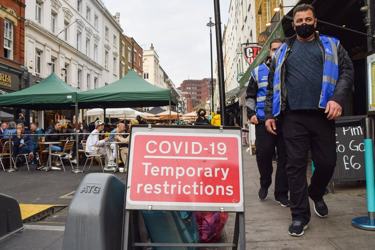 People walk past a COVID restrictions sign on a city street