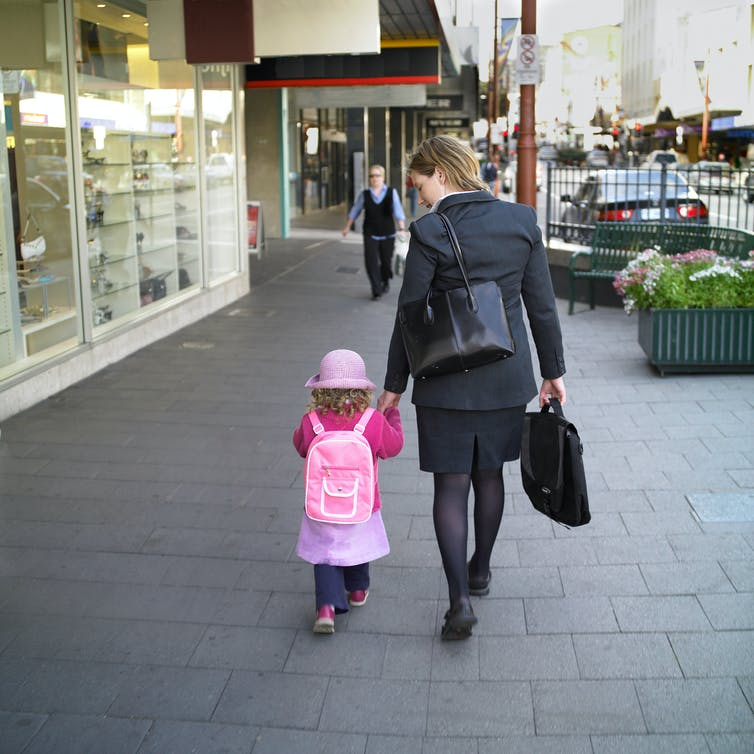 Women in professional wear carrying a briefcase as she takes a young girl to childcare