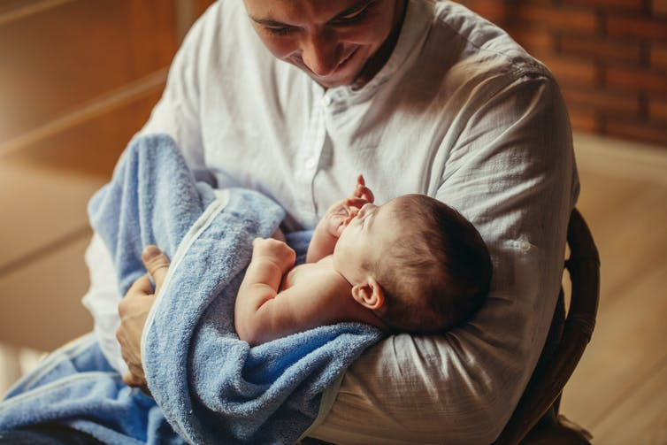 Father cradles young baby wrapped in towel in his arms