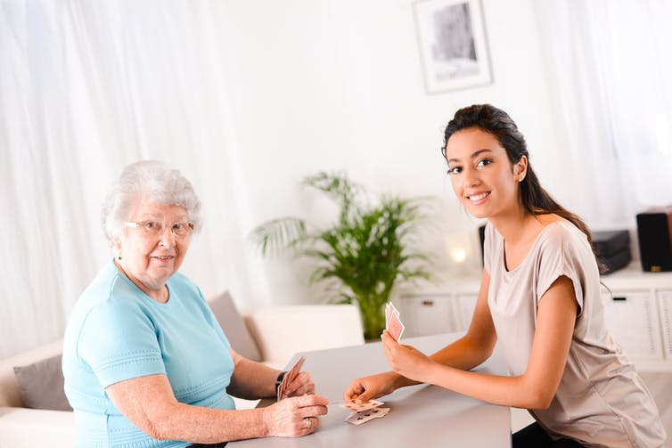 An older woman playing cards with a younger woman