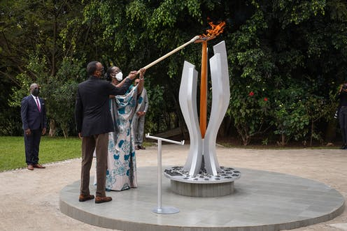 A man and a woman, both wearing face masks, hold a pole to light a flame on a monument in a garden.