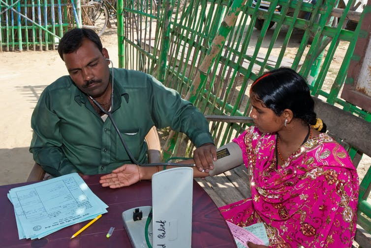 Woman examined by doctor in rural Indian clinic.