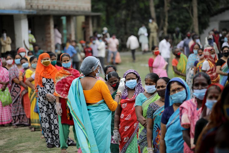 Indian women stand in a queue wearing masks.