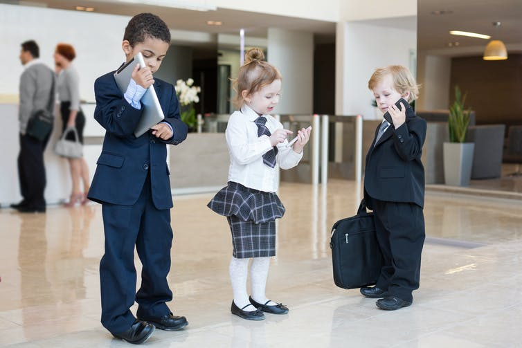 Three children dressed as if they're workers in an office