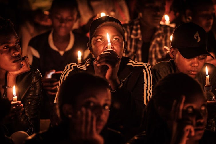 A crowd of people in the dark, lit by candles that they hold.