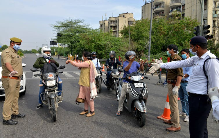 Police in India stopping commuters to ask why they are out during lockdown, New Delhi, India, March 24 2020.