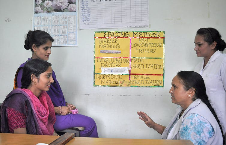 Women sit talking to one another in front of a poster depicting contraceptive methods.