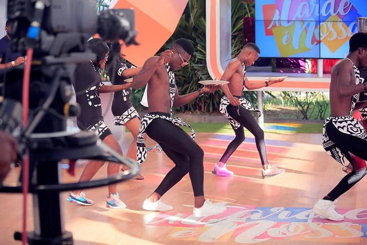 A television studio, a large camera foregrounded. In front of the cameras, a group of young men dances.
