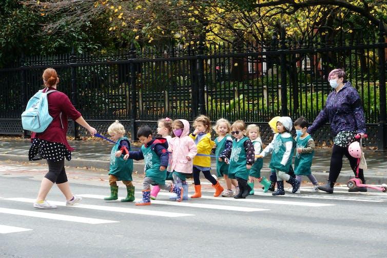 Line of pre-school students cross a street