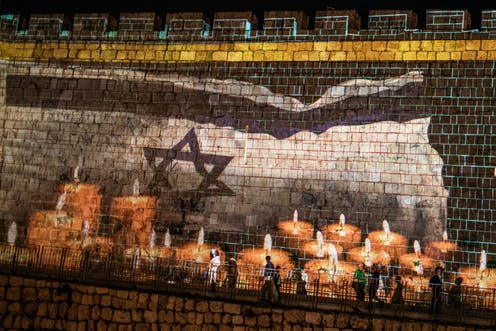 A condolence message and candles for the victims of a stampede during a Jewish ultra-Orthodox mass pilgrimage to Mount Meron is projected on a wall of Jerusalem's Old City.