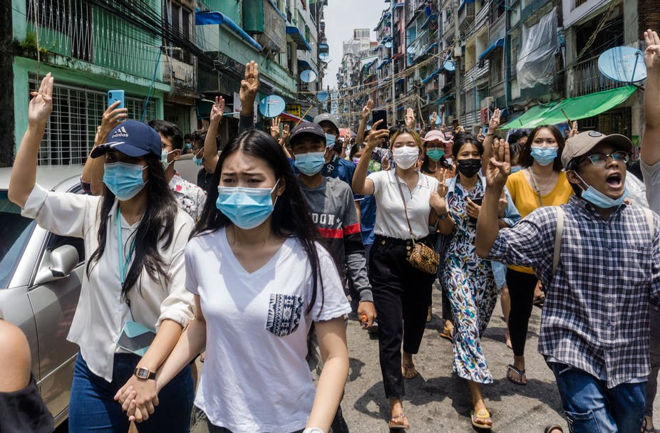 Burmese women wearing face masks march on the streets, wearing face masks