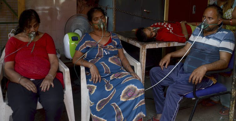 Four people receive oxygen, three sitting in chairs and another lying on a table.