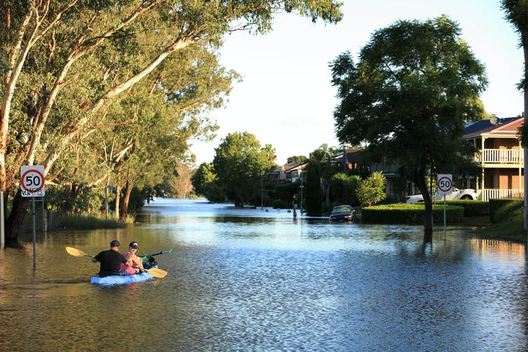 A man and woman use a kayak to travel up a flooded street.