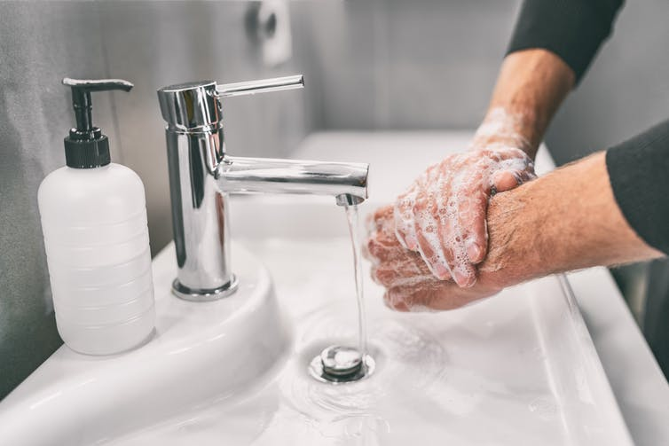 A man washes hands.