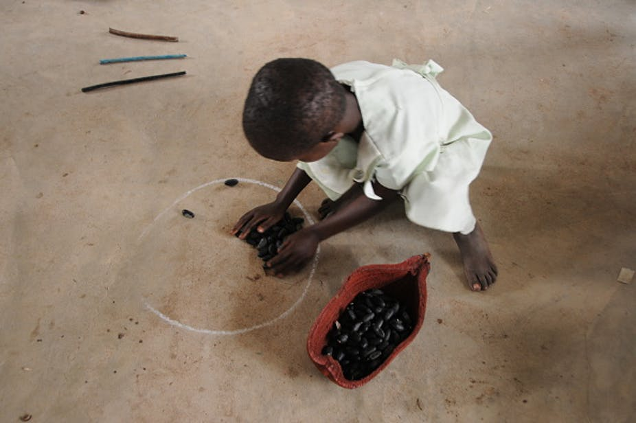 A child playing with baobab seed pods on the ground.