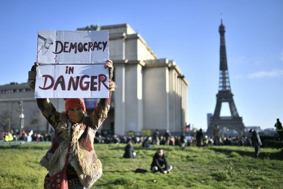 Une femme brandit une pancarte «Démocratie en danger» à Paris