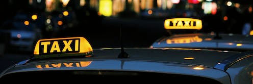Two taxis on a street at night