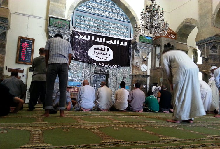 Un groupe d'hommes priant dans une mosquée de Mossoul, avec un grand drapeau noir et blanc de l'État islamique sur le mur.