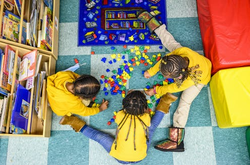 Three children play together at daycare center