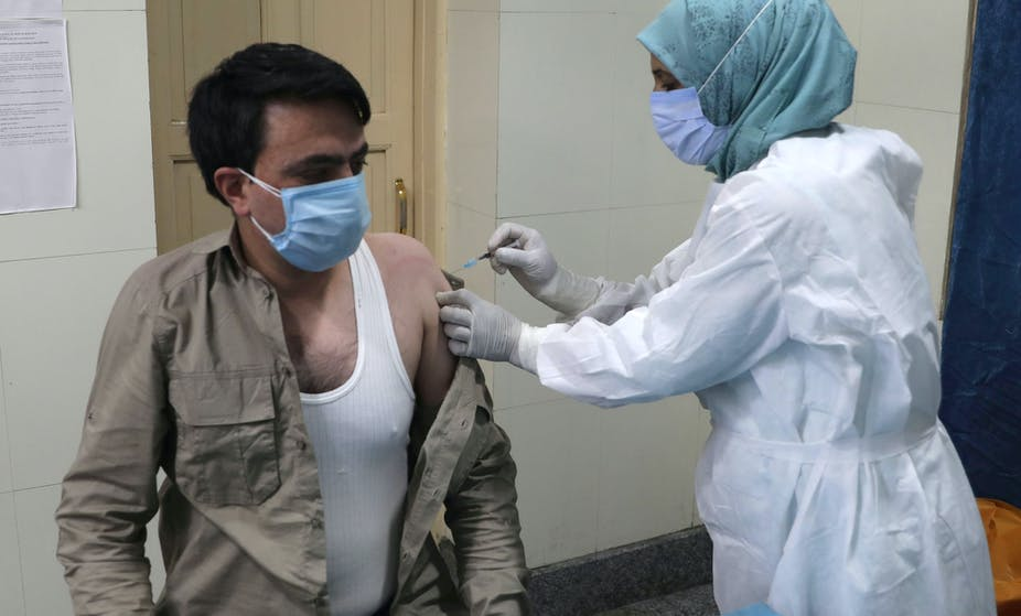 A man in India being vaccinated by a nurse