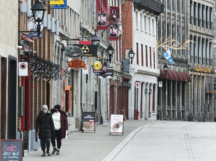 Two people wearing masks walk along a street.