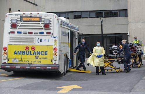 Paramedics wheeling gurneys to an ambulance bus in a parking lot