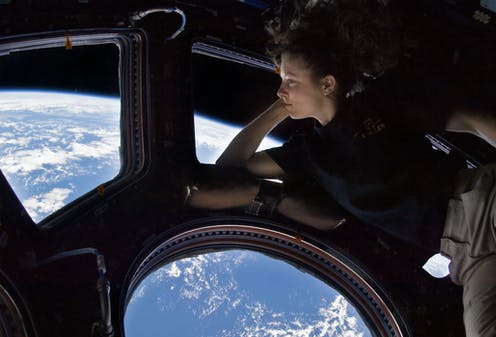 A woman in a windowed room looking at the earth from space.