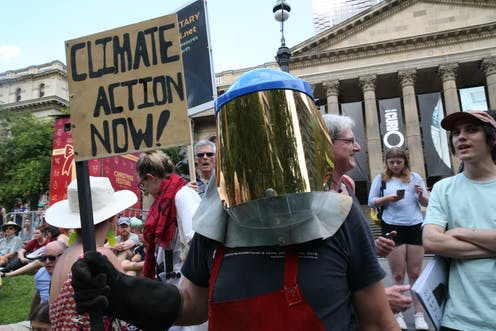 Protester in a mask holding up a sign that says 'climate action now'