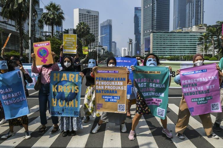 Lima orang aktivis lingkungan membawa spanduk berwarna-warni berdiri di trotoar.