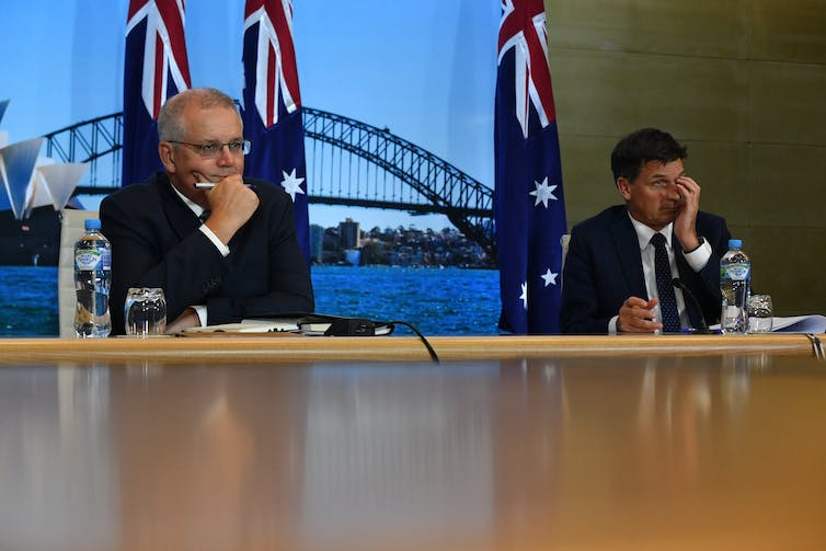 Scott Morrison and Angus Taylor sit with hands on their faces in front of Australian flags