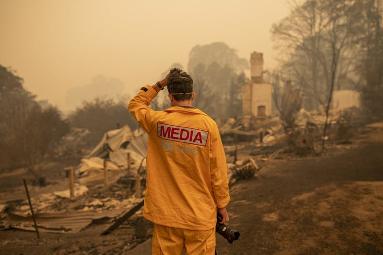 A man in a yellow shirt reading MEDIA looks at a property destroyed by fire.
