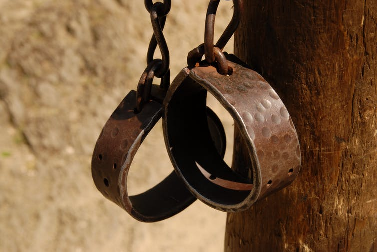 Metal chains with hand shackles hanging off post
