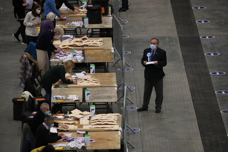 Ballots being counted while Alex Salmond watches on.