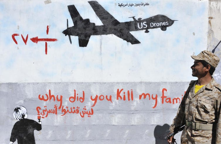 A Yemeni soldier looks at the graffiti of U.S. drone strike painted on a wall as a protest against the drone strikes, in Sanaa, Yemen