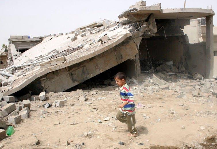 A boy runs past a damaged house.