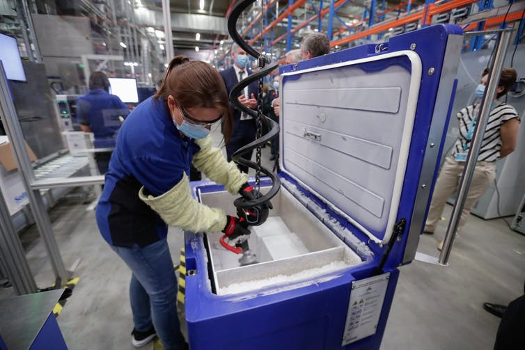 A worker in a vaccine manufacture plant packs doses.