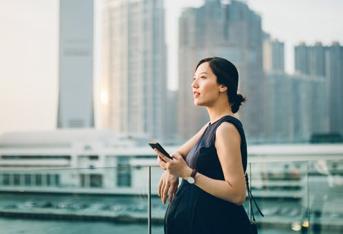 pregnant woman outdoors holding phone
