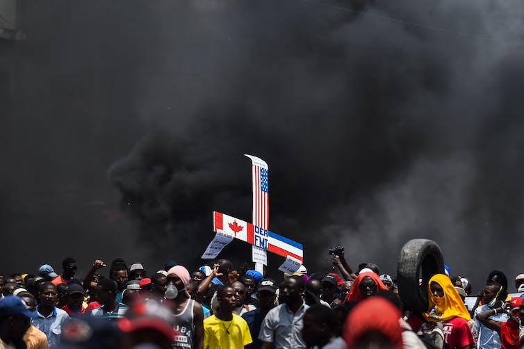 La folla in strada sotto un cielo fumoso sorregge un cartello con bandiere statunitensi, canadesi e altre bandiere straniere
