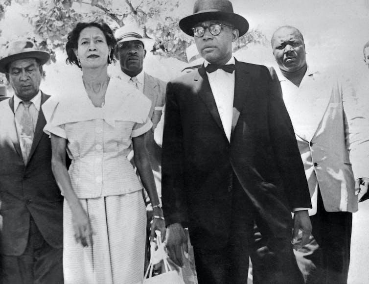 Immagine in bianco e nero di François Duvalier, in giacca e cravatta, e sua moglie, in abito, circondati da uomini vigili