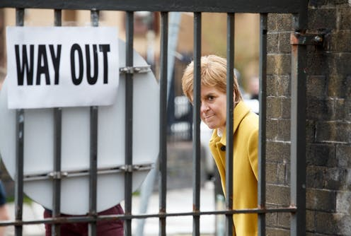 Nicola Sturgeon looks out from behind a gate with a 'way out' sign on it.