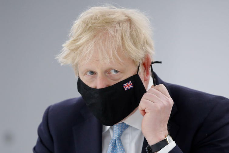 Boris Johnson wearing a face mask with a union flag embroidered onto it.